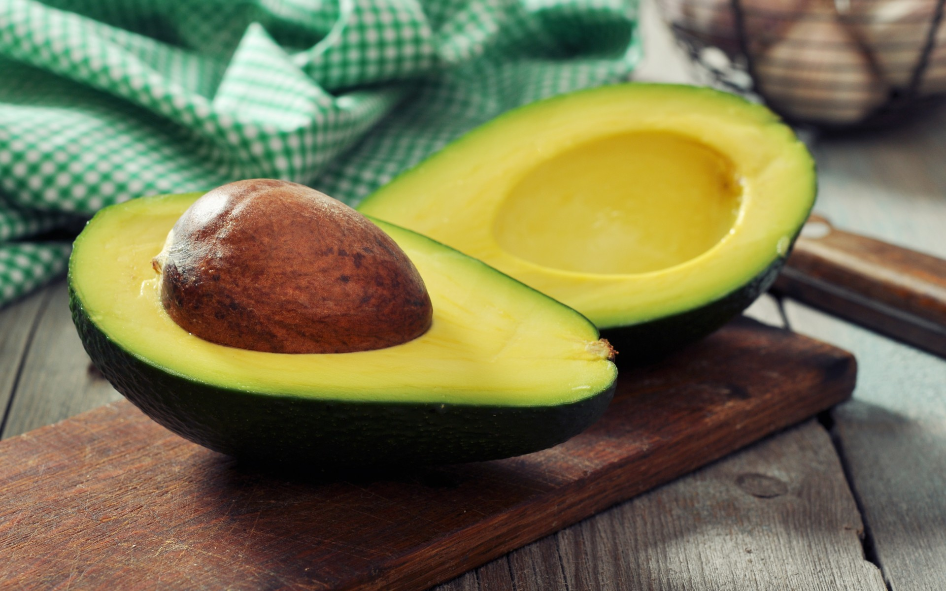 avocado cut in half, core, tablecloth,knife