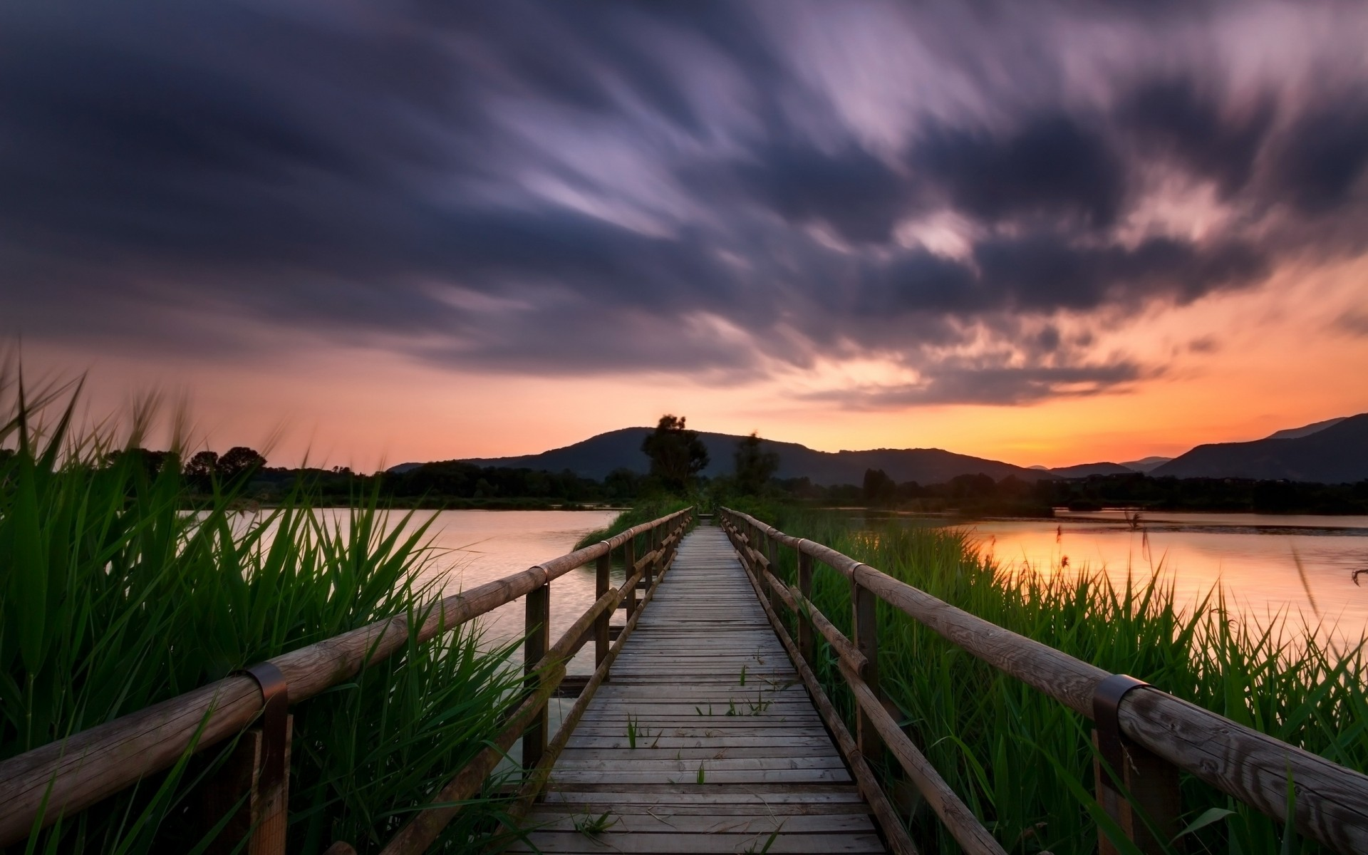 colorful sky, trellis bridge, lake,  grass